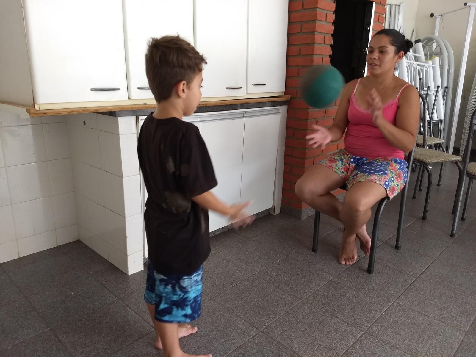 Aline Honório, de 28 anos, brinca com o filho mais velho no quintal da Casa de Missão Amor Gratuito. (Foto: Ederson Hising/G1 PR)