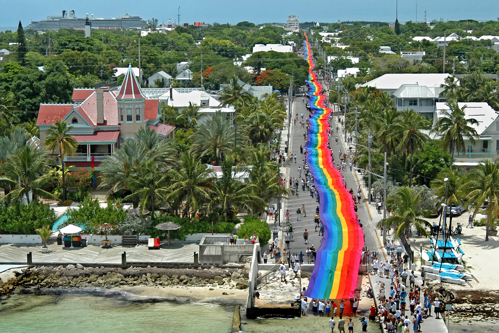 In this file photo, carriers reach the Atlantic Ocean Sunday, June 15, 2003, as they  finish carrying a 1 1/4-mile-long rainbow flag down Duval Street in Key West, Fla. The mammoth banner was created by Gilbert Baker and commemorated the 25th anniversary of the LGBT icon that Baker conceived in 1978. Baker, at age 65, was found deceased March 31, 2017, in New York City. Photo by Andy Newman/Florida Keys News Bureau/H0)