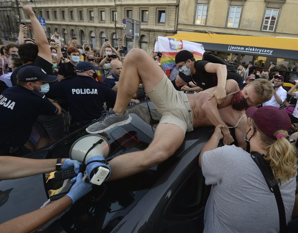 7 de agosto - Ativista sobe em carro da polícia para protestar contra a detenção de ativista LGBT em Varsóvia, na Polônia. O incidente ocorre em meio a tensões crescentes na Polônia entre ativistas LGBT e governo conservador que se opõe aos direitos LGBT — Foto: Czarek Sokolowski/AP