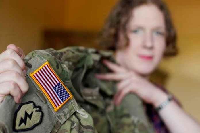 Transgender U.S. Army captain Jennifer Sims lifts her uniform. AP Photo/Matthias Schrader